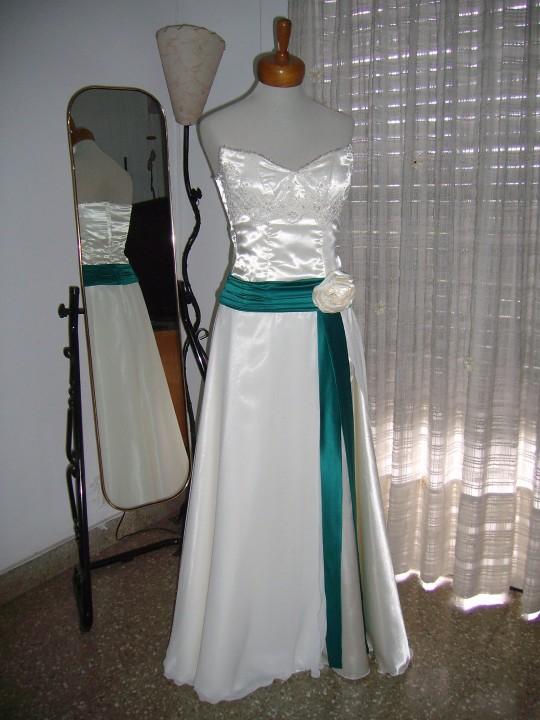 Vestido en satén, muselina y encaje. Ornamentado con faja drapeada, bordados, lazo y flor artesanal.